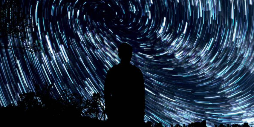 A silhouette watches swirling stars.
