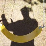 A man's shadow over a swing set
