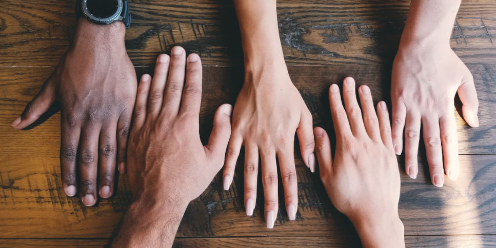 Multiracial hands on a table