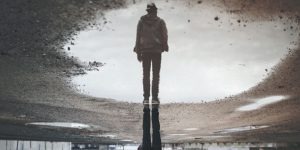Image of a man reflected in a puddle.