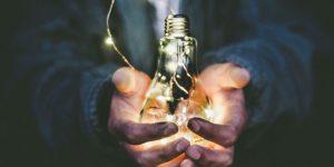 A man holding an incandescent bulb