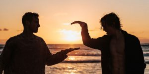 Two men about to shake hands in the sunset.