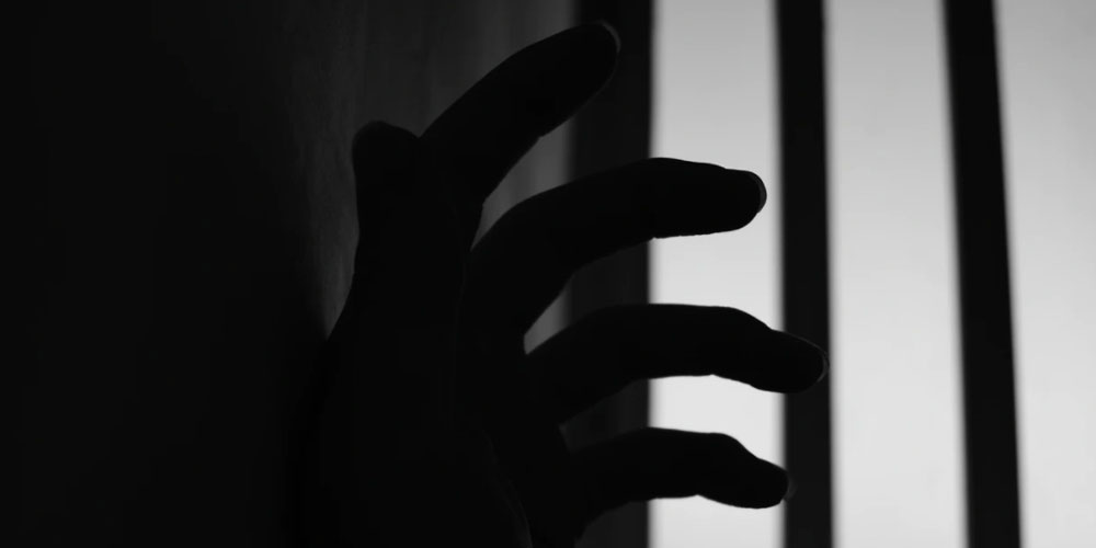A hand and barred window