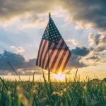 American flag in a field at sunset