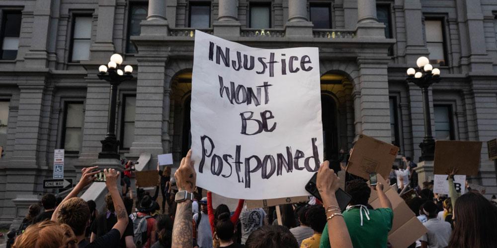 """Injustice Won't Be Postponed"" sign"