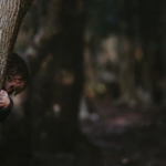 A child hides behind a tree