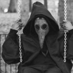A man in a plague mask on a swing