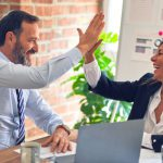 A man and woman high five in an office