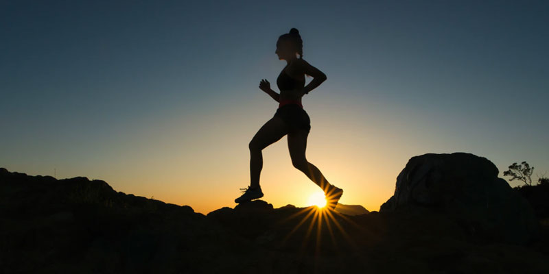 Woman running in the dessert at dusk