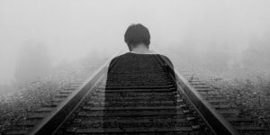 A fading man on train tracks