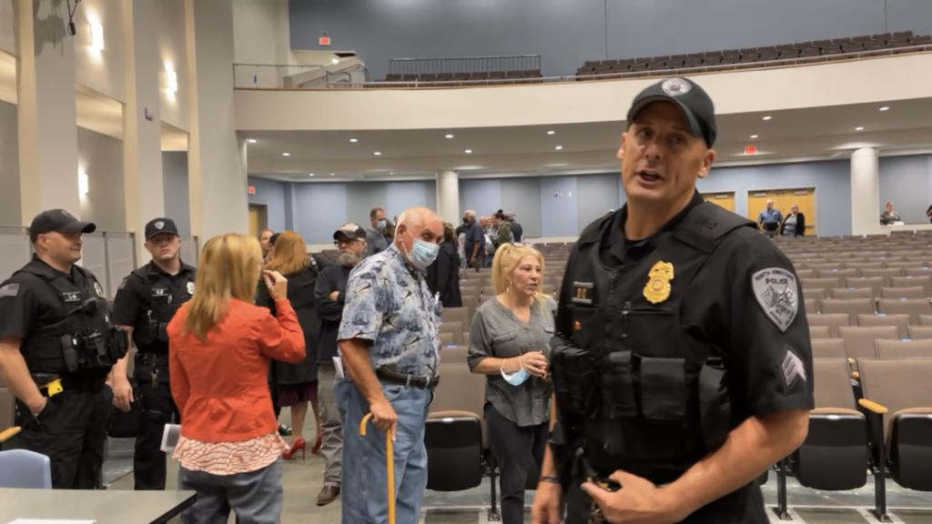 Police and protesters at NK school committee meeting